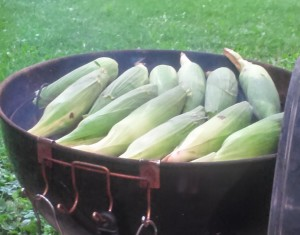 Picture of a charcoal grill with corn on the cob.