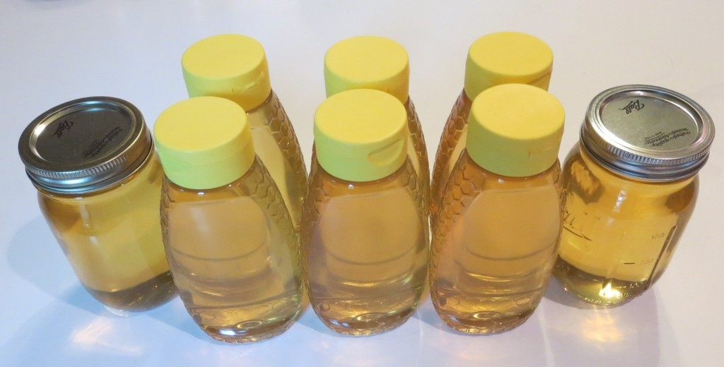 mason jars and plastic bottles filled with honey
