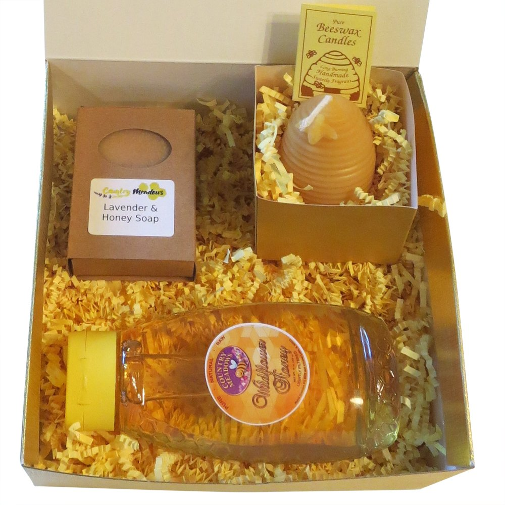 A picture of a honey gift box including a one pound jar raw wildflower honey, a handmade skep beeswax candle and a bar of lavender and honey soap.