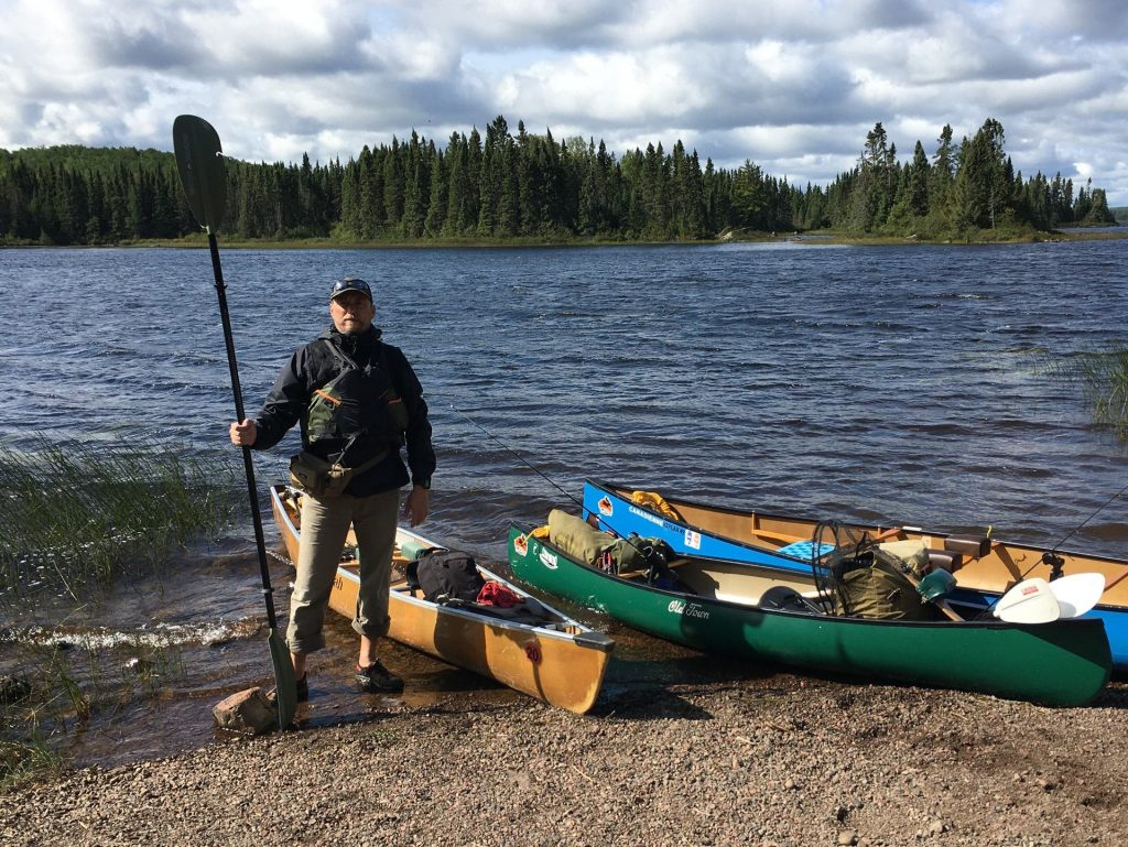 standing in front of canoe with double blade paddle