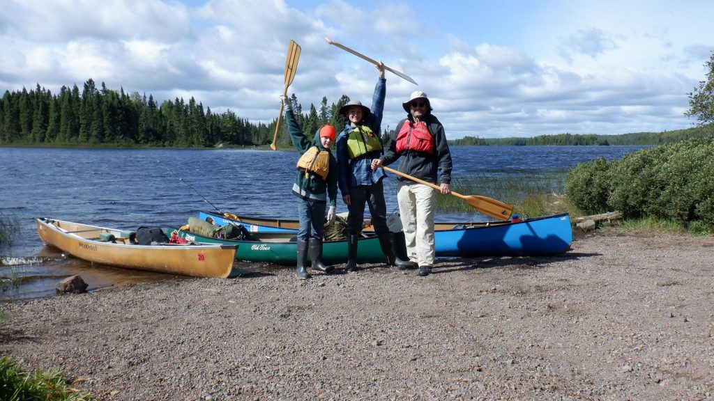 father and sons ready to launch canoes