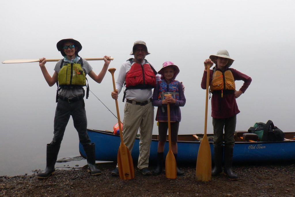 4 canoeists at shore of lake